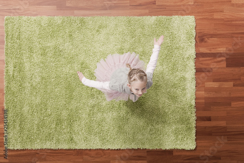germany, cologne, girl (6-7) playing on carpet, looking up, elevated view