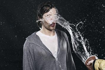 Junger Mann bekommt ganz schön viel Wasser ab, pitschnass