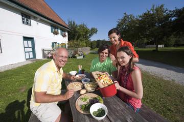 Deutschland, Bayern, Menschen am Tisch im Garten die Zubereitung zubereiten Essen von Speisen
