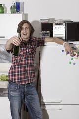 Deutschland, Junger Mann in der Küche mit Bierflasche, Porträt