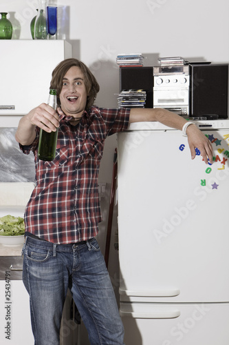 germany, berlin, young man in kitchen holding beer bottle, portrait