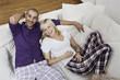 Deutschland, Junges Paar sitzen auf dem Sofa, lächeln,