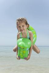 Spanien, Mallorca, Mädchen am Strand mit inflatable, Springen