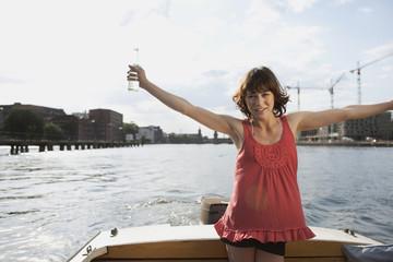 Deutschland, Berlin, Frau jung am Motorboot, Arme ausstrecken