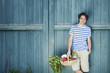 germany, bavaria, man in front of barn door holding basket with fresh vegetables, smiling, portrait