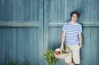 Deutschland, Bayern, Mann vor der Stalltür halten Korb mit frischem Gemüse, lächeln, Porträt