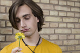 germany, berlin, young man in front of brick wall holding flower, portrait, close-up