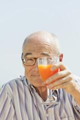Spanien, Mallorca, Senior Mann halten Glas mit Orangensaft, Porträt