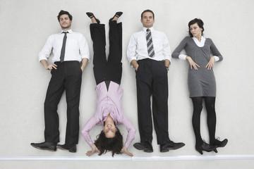 Vier Geschäftsleute, die nebeneinander stehen, eine Frau beim Handsteht