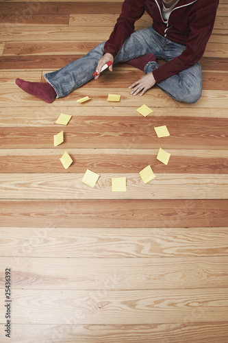man sitting besides a circle of adhesive notes