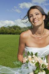 Deutschland, Bayern, Braut im Park mit Blumen, Porträt, Nahaufnahme