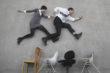 Geschäftsmann und Geschäftsfrau Hand in Hand, springen über Stühle