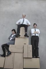 Drei Geschäftsleute auf Umzugskisten, ein Geschäftsmann trägt Krone, Lächeln