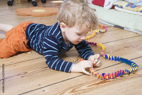 germany, berlin, boy (3-4) lying on floor, playing with streamer