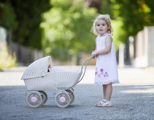 Deutschland, Bayern, Mädchen spielt mit Spielzeug-Kinderwagen