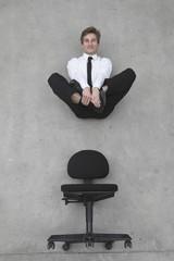 Geschäftsmann schwebt über Stuhl, lächelnd, Porträt
