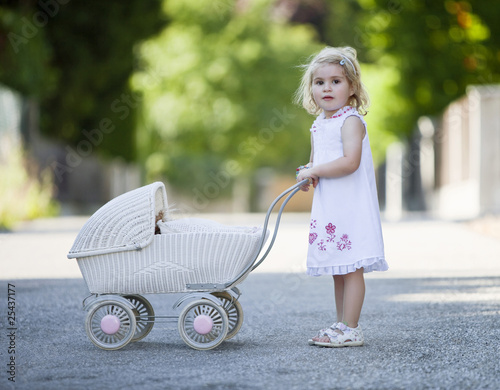 germany, bavaria, girl (2-3) playing with toy baby carriage