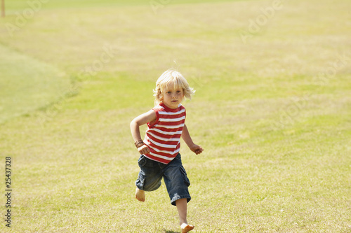 spain, mallorca, boy (3-4) running across meadow