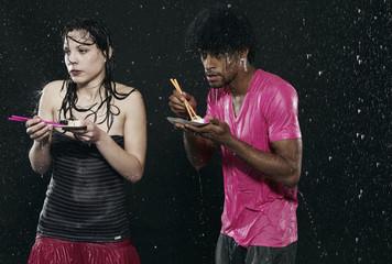 Mann und Frau essen im Regen