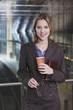 Deutschland, lächeln Bayern, München, Geschäftsfrau Frau im U-Bahnhof halten Pappbecher, Portrait