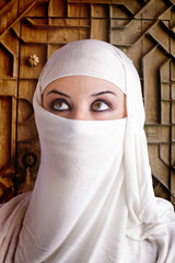 woman dressed in Arab costume, castle gate in the background