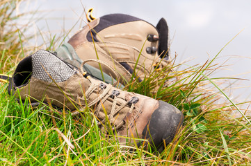 Old hiking boots close-up on green grass