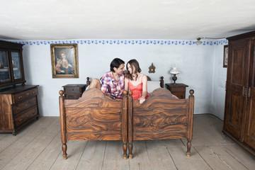 Deutschland, Bayern, Junges Paar in rustikal Schlafzimmer