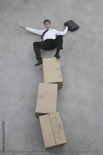 businessman balancing on stack of cardboard boxes, portrait, elevated view