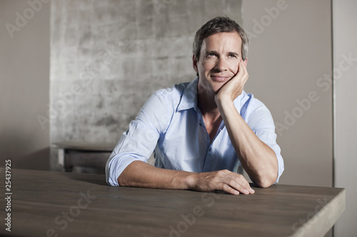 germany, hamburg, man sitting at table, contemplating, portrait