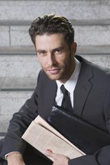 Deutschland, Bayern, München, Geschäftsmann Mann sitzen auf Treppe mit Zeitung, Portrait