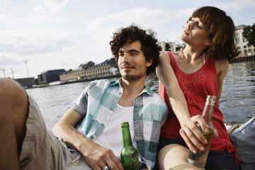 Deutschland, Berlin, Junges Paar auf dem Motorboot, mit Flaschen, Portrait, close-up