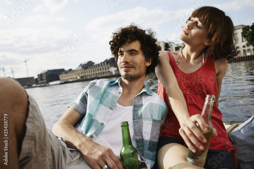 germany, berlin, young couple on motor boat, holding bottles, portrait, close-up