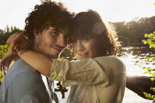 germany, berlin, young couple embracing by river spree,  side view, portrait, close-up