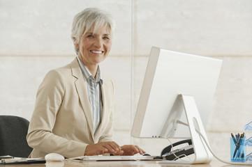 Ältere Geschäftsfrau mit Computer