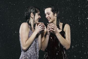 Freunde, zwei junge Frauen, stehen im Regen, Wetter, mit Heißgetränk