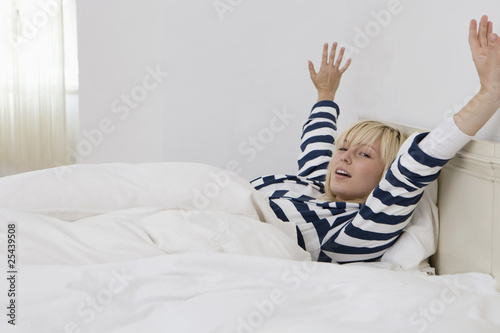 germany, berlin, young woman in bed waking up, portrait