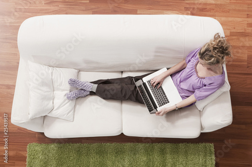 germany, cologne, woman on sofa using laptop, elevated view