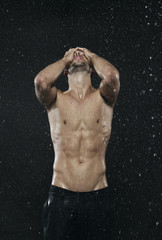 Sportlicher Mann steht im Regen, Wetter, freier Oberkörper, Haut, nackt