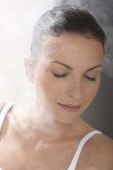 Frau entspannt in Dampfbad, die Augen geschlossen