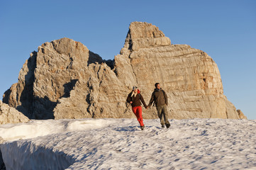 Österreich, Steiermark, Dachstein, Junges Paar beim Wandern auf dem Berg, Hand in Hand
