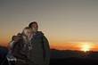 Österreich, Steiermark, Dachstein, Paar steht auf Berg bei Sonnenuntergang, lächelnd