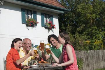 Deutschland, Bayern, vier Personen trinken Bier im Garten, Spaß, Portrait