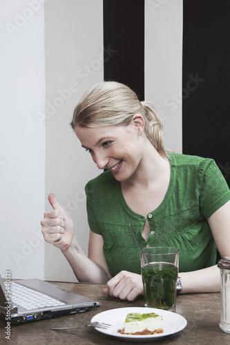 Frau schaut auf Laptop machen Daumen nach oben