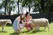 Deutschland, Bayern, Zwei Frauen auf der Weide füttern Schafe, lächeln, Porträt