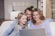 Deutschland, Familie auf dem Sofa mit Laptop, Portrait