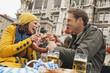 Deutschland, Bayern, München, Paar halten Brezel, lachen, Porträt