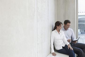 Deutschland, Köln, Zwei Business-Leute sitzen auf der Bank, mit Terminkalender