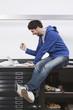 Mann sitzen auf dem Schreibtisch mit Laptop, gestikulieren
