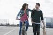 Deutschland, Berlin, Junges Paar mit Fahrrad und Papiertüte