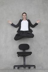 Geschäftsfrau schwebt über Stuhl